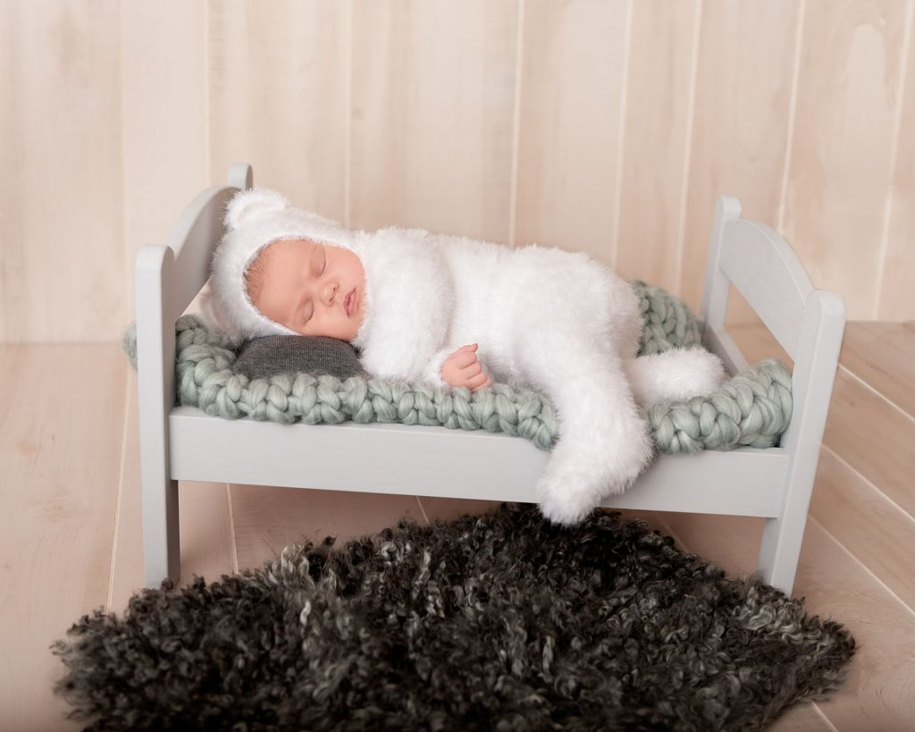 Newborn portrait session with a little newborn wearing a fuzzy bear sleeper while in a tiny bed. Photograph taken in Maple Grove, Minnesota
