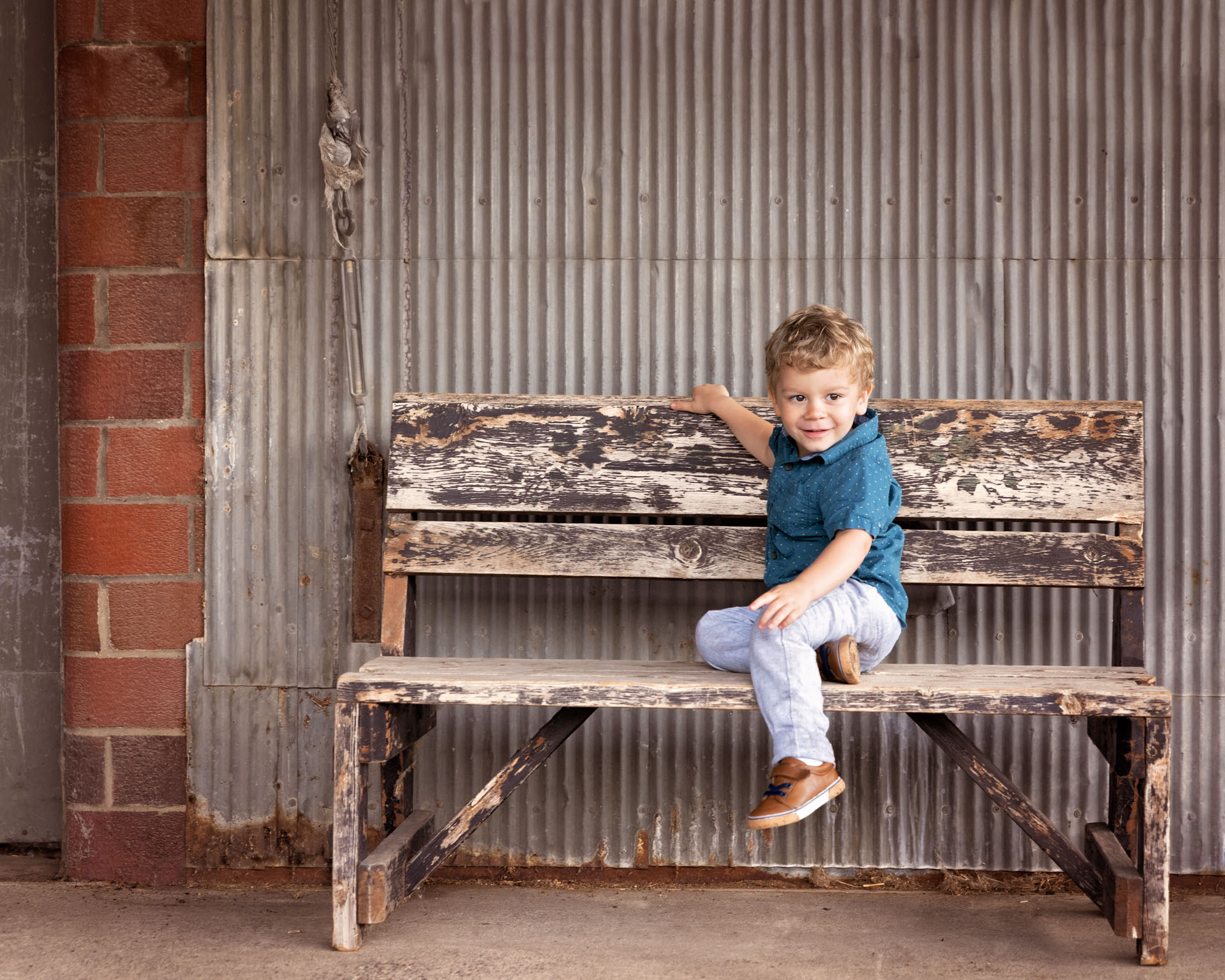 On the farm children's portrait photography with birthday boy sitting on bench in Andover, MN