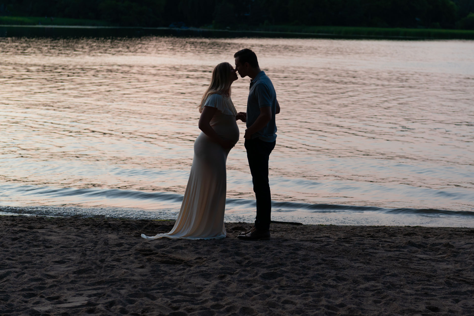 A quiet moment together during their sunset maternity photo shoot in Plymouth. Gown provided by Addie Lane Studios.