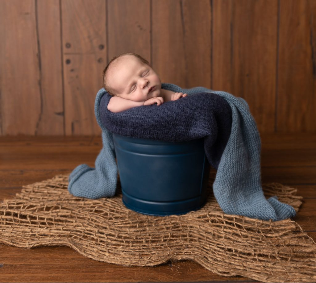 Baby boy posed in a blue bucket during his newborn portrait session by Addie Lane Studios in Maple Grove, MN