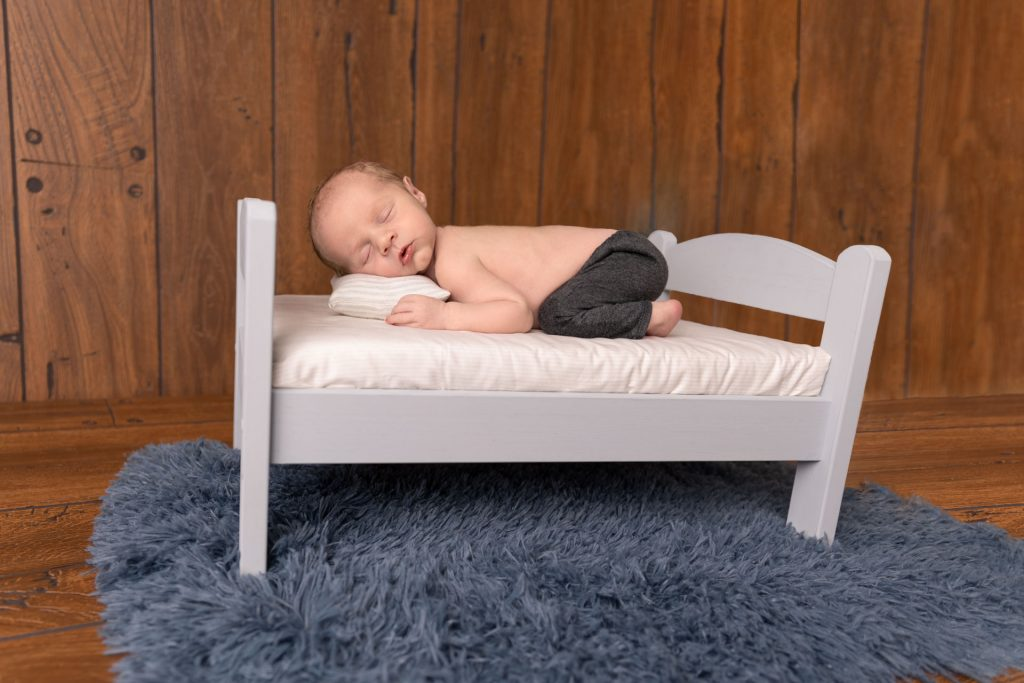 Baby boy sleeping on little bed during newborn photography session in Maple Grove, MN