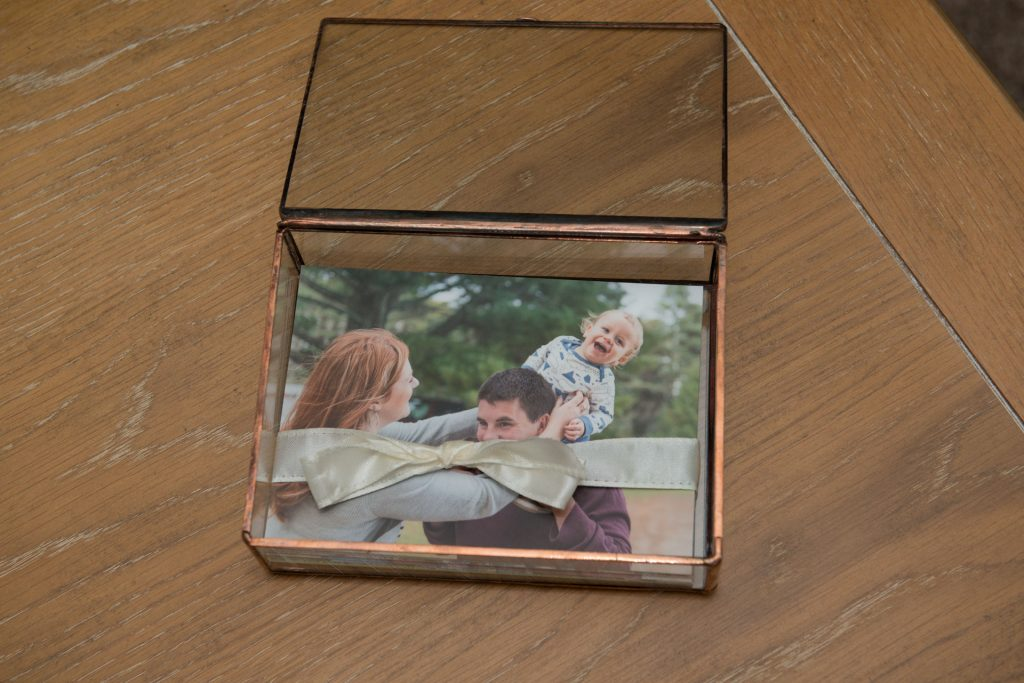 Glass keepsake folio box contains printed images of a family photo session